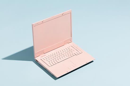 pale blue desk with a pale pink open laptop