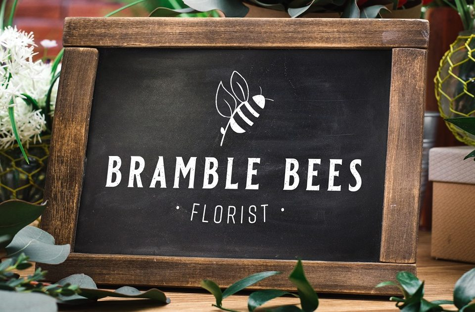 chalk board with a business logo in white saying Bramble Bees Florist
