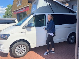 white T6 VW Transporter with pop top and tall lady stood beside it